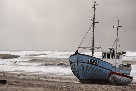 fishing boat on the beach during storm in Nr. Vorupør on the North Sea coast in Denmark Archivio Fotografico
