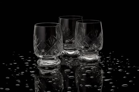 Transparent empty wineglasses for vodka with reflection and drops on a black background Banco de Imagens