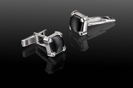 silver cufflinks with black stones on a black background with reflection