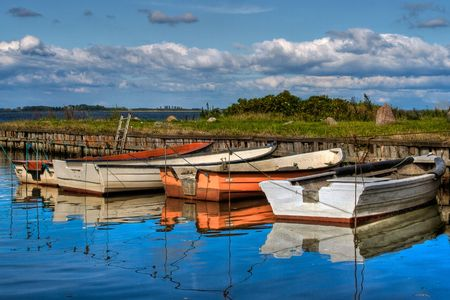 Small fishing boats in natural harbor HDR