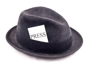 An old fedora felt hat with press card Imagens