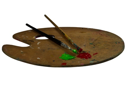 Two brushes on a palette with green and red paint. Isolated on white