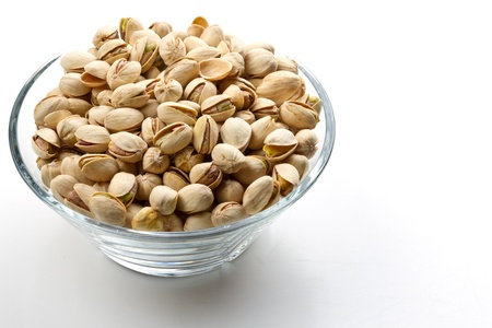 Pistachios nuts in glass bowl with white background