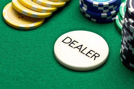Poker dealer button and chips on green felt photo