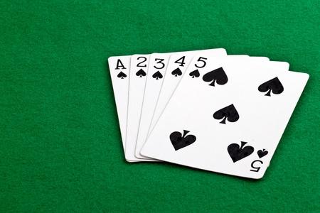 Poker hand with a straith flush of spades on green felt