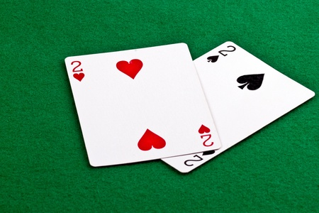 Poker hand with a pair of deuces on green felt Stock Photo