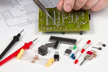 microprocesadores: Ingeniero de soldadura de la placa de circuito rodeado de componentes de repuesto Foto de archivo