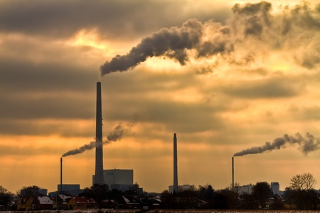 Winter scenic of power plant with a burning yellow sky behind Stock Photo