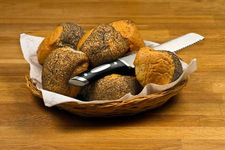 Fresh Bread Rolls and knife  In Basket on wooden table