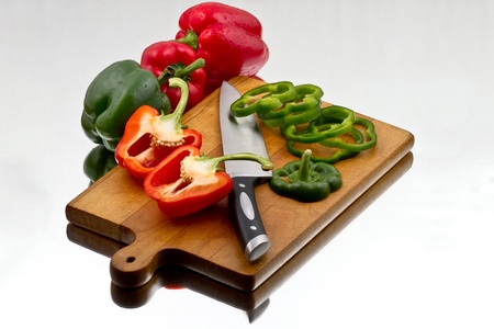 Red and green bell peppers being chopped at wooden cutting board with knife. Surrounded by hole bell peppers on reflective background Stock Photo