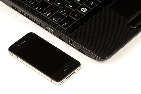 Close-up of a black smartphone and a black laptop on white background