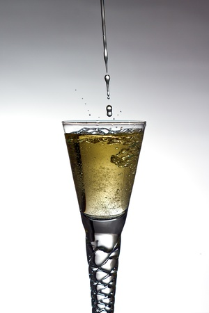 Champagne pouring into glass on gratuated background
