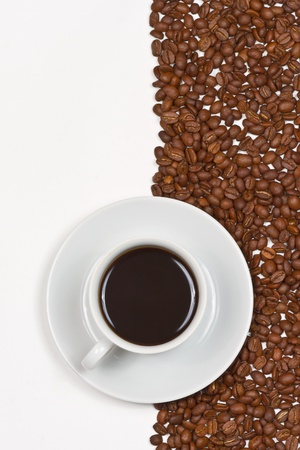 Coffee in white cup on saucer placed on background of cofee beans and white photo