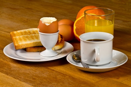 Breakfast: Boiled egg, toast, coffee and fresh orange juice. On Wooden table photo