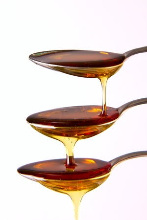 Syrup cascading down the spoons Stock Photo