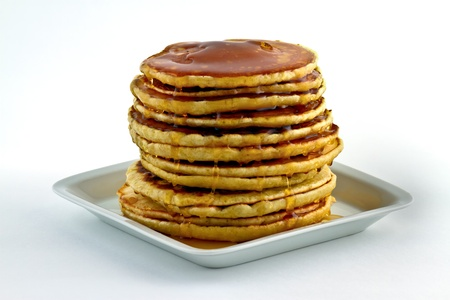 Pancakes with syrup poured over at dish on white background