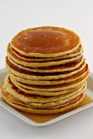 Stack of homemade pancakes with syrup on a white plate. Stock Photo