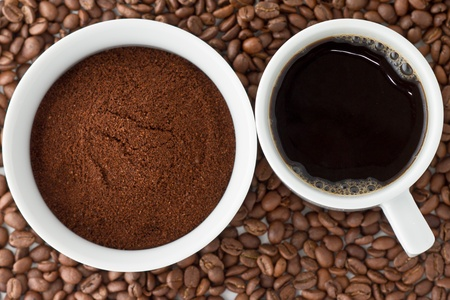 grinded: Coffee power in bowl and coffee in cup on top of coffee beans