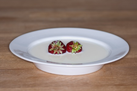 White saucer with fresh strawberries in milk with sugar poured over. Placed on wooden table