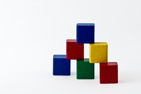 colorful wood building blocks stacked as pyramid. Isolated on white Stock Photo