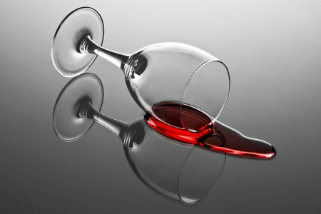 Wine glass with red wine tumbled over and wine spilled out on reflecting surface Stock Photo