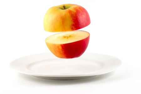 Sliced Apple hovering over white plate