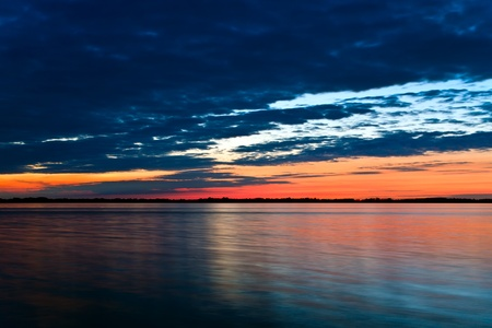 Scenic seascape view at sunset with cloudscape background.