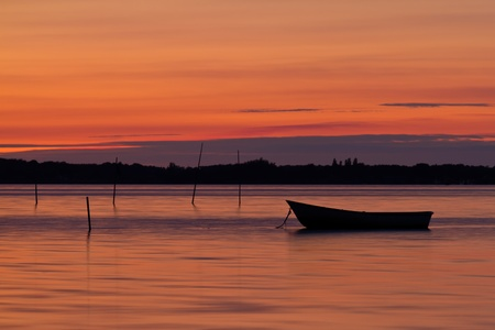 Scenic view of small fishing boat at sunset with cloudscape background.