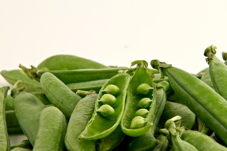 sweet sugar snap: Bunch of green peas  with one open pod.