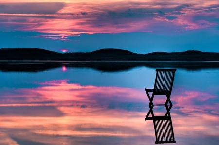 Toneel mening van zonsondergang over de inlaat en heuvels met een stoel in het kalme water, met weerspiegelingen van zonsondergang en stoel. Symboliseert vrede, eenzaamheid of emptyness