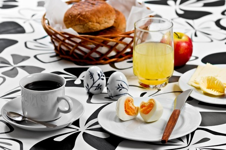 Breakfast with heart shaped egg, coffee, orange juice, bread, butter, cheese and an apple Stock Photo
