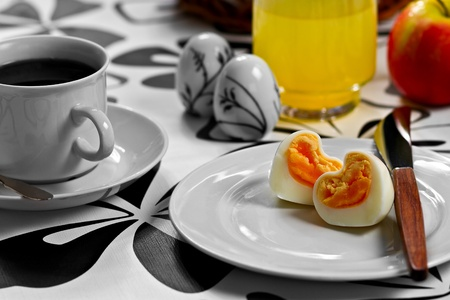 Breakfast with heart shaped egg, coffee, orange juice and an apple photo