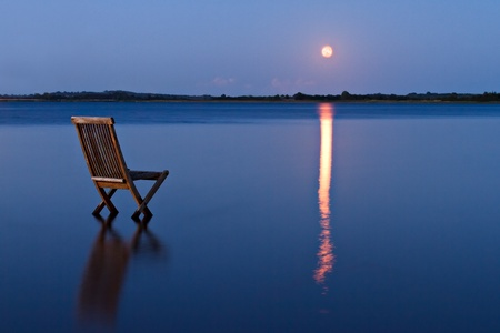 Singular chair in calm water facing the land in the horizon. With rising orange moon reflected in the blue water Stock fotó