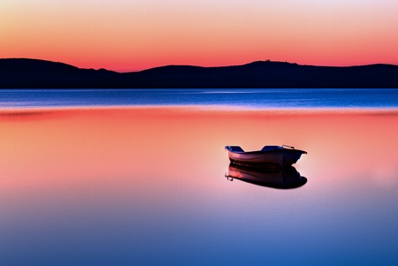 Scenic view of small fishing boat in calm water at sunset with hills in the background.