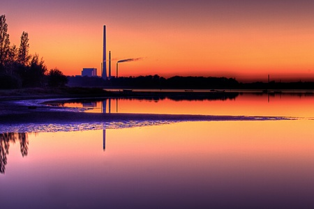 Scenic view of power plant near beach in calm water at sunset
