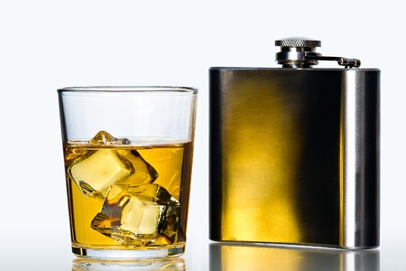 glass of whisky on the rocks  and stainless flask on white background Stock Photo