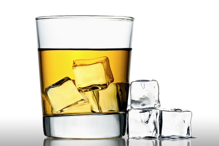 glass of whisky on the rocks with ice cubes next to, isolated on white Stock Photo
