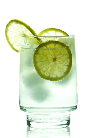 Glass of gin and tonic with ice cubes and lime slices. isolated on white photo