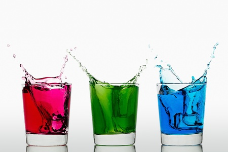 Ice cubes falling into three glasses with different colored liquid Stock Photo