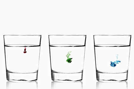 Red, green and blue food color diffusing into three glasses of water.