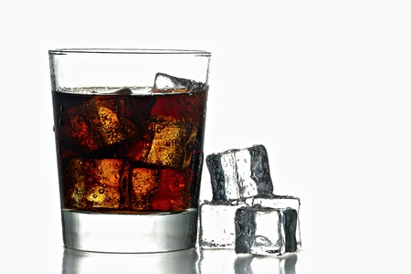 glass of fresh icy cold cola with ice cubes next to
