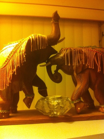 decor: Wooden elephant decor on shelf.
