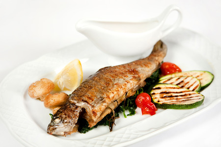 Grilled dorado with herbs, champignons, lemon, cherry tomatoes and vegetable marrows photo