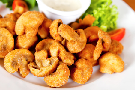 Deep-fried champignon mushrooms with lettuce, tomatoes and mayonnaise Stockfoto