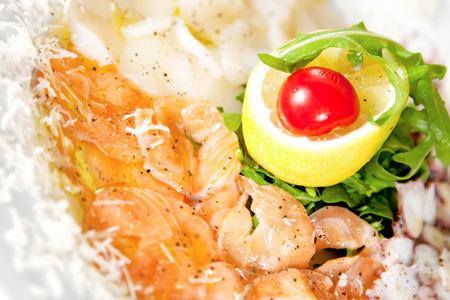 Salmon and dorado carpaccio with rucola, lemon and cherry tomato photo