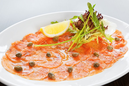 Salmon carpaccio with rucola, lemon and lettuce Фото со стока