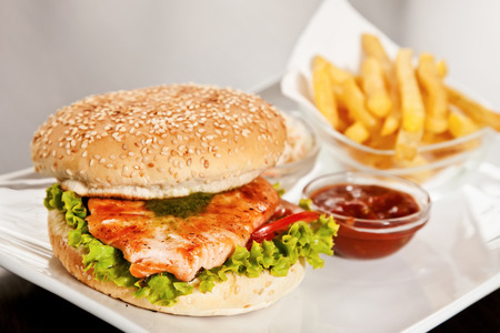 Burger with salmon, lettuce, tomatoes and deep-fried potato photo