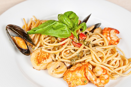 deepsea: Linguine pasta with mussels, prawns, deep-sea scallop, tomatoes, capers and basil Stock Photo
