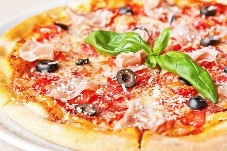 Pizza with prosciutto, olives, tomatoes, parmesan cheese and basil photo