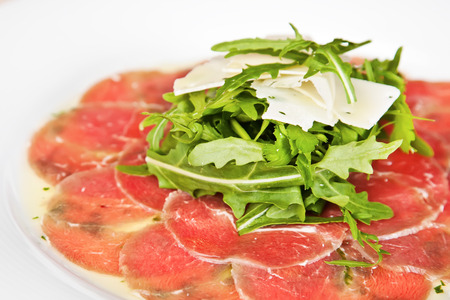 Veal carpaccio with rucola, parsley and cheese Standard-Bild